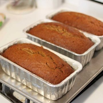 Three loaves of fresh pumpkin bread are ready for the freezer in disposable aluminum bread pans.