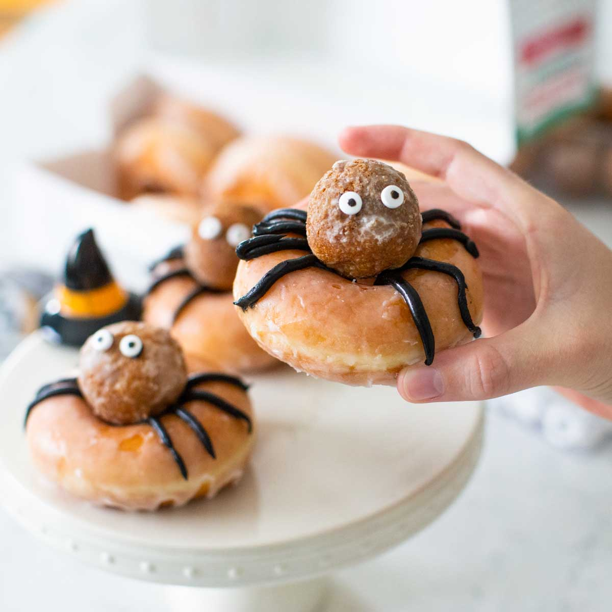 A glazed donut decorated to look like a spider with a donut hole on top, googly eyes, and black frosting legs is in the hand of a kid.
