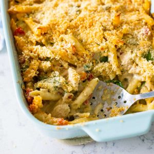 A blue baking dish filled with alfredo pesto pasta and topped with crunchy breadcrumbs. A slotted spoon has scooped out a serving.
