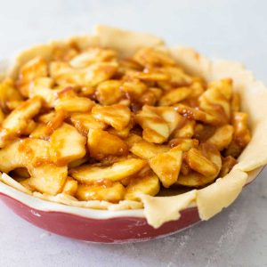 A deep dish pie pan has pie crust draped over the side and a mound of sliced apples coated in cinnamon and butter.