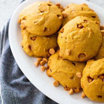 A platter of puffy pumpkin butterscotch cookies with a sprinkle of butterscotch chips sits next to a denim napkin.