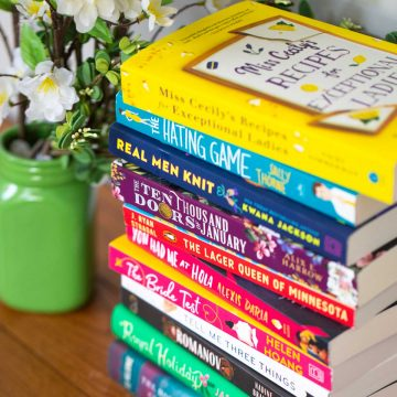 A stack of colorful book club fiction books next to a green vase of flowers.