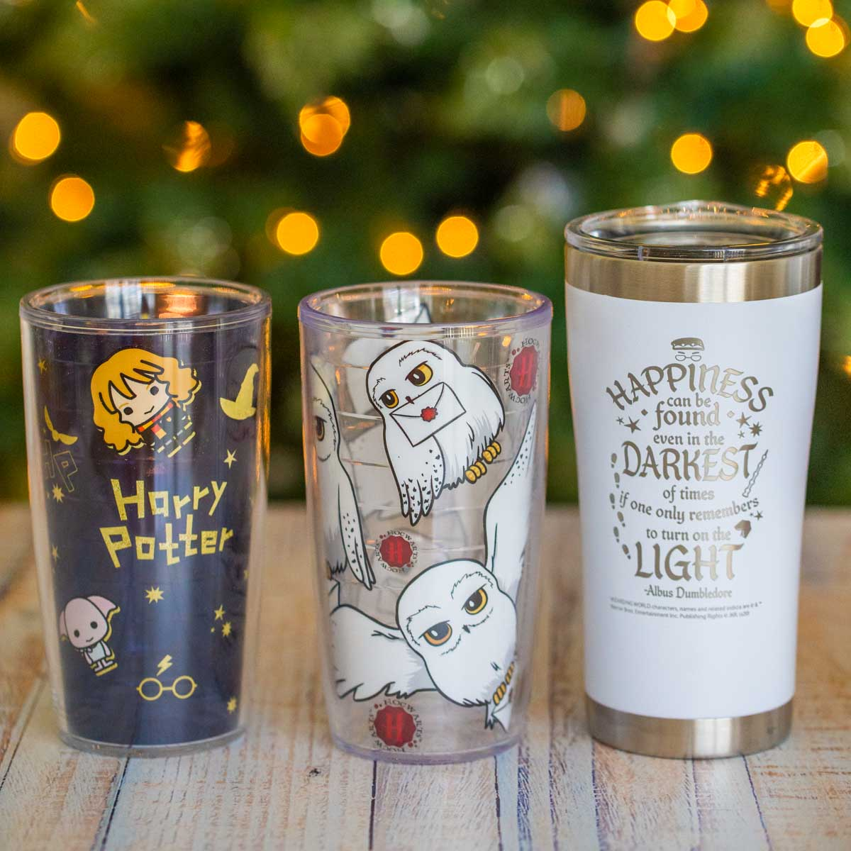 Three Harry Potter tumblers in front of a lit Christmas tree.