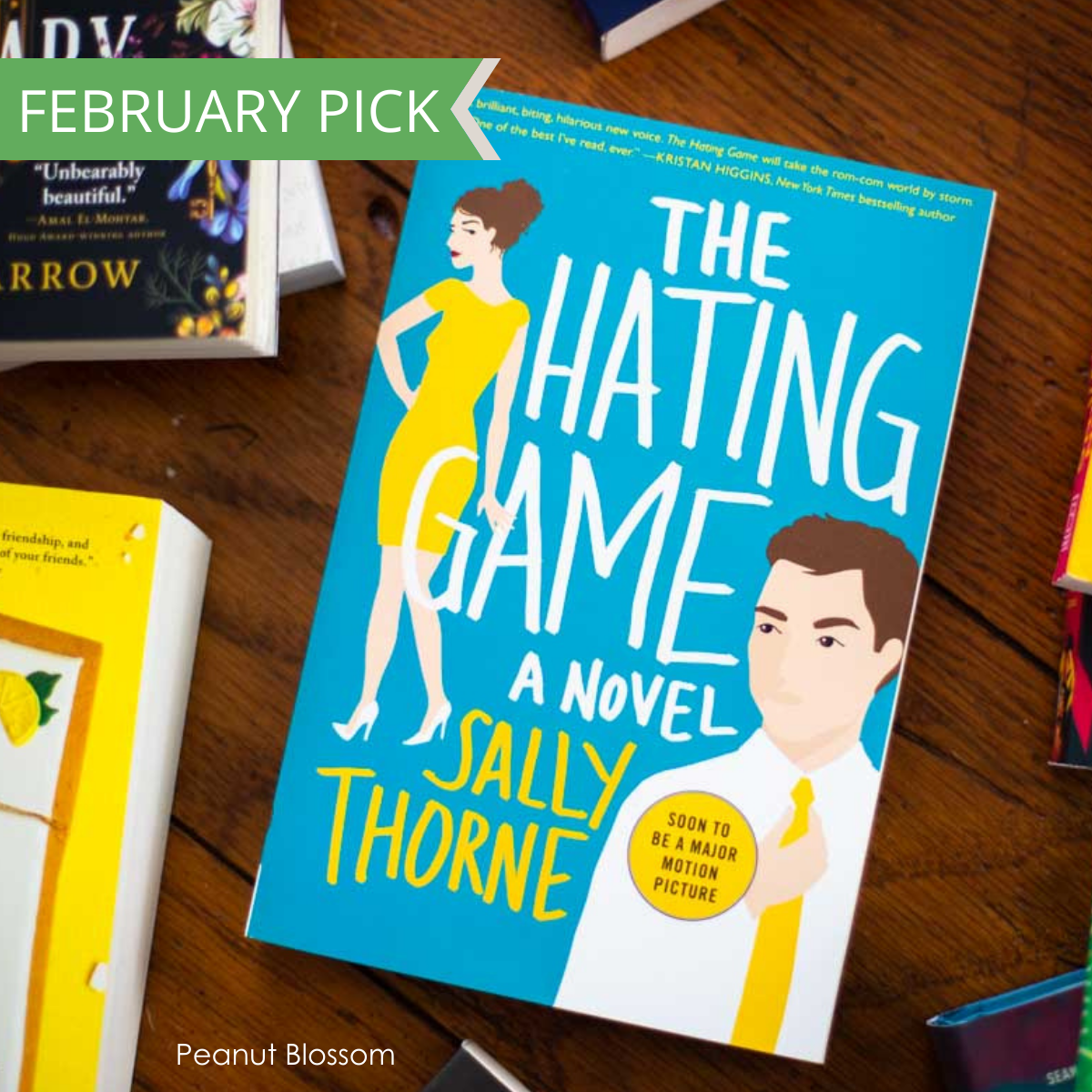 The cover of the book The Hating Game sitting on a table surrounded by other books.