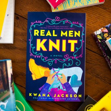 Cover of the book Real Men Knit by Kwana Jackson sits on a table.
