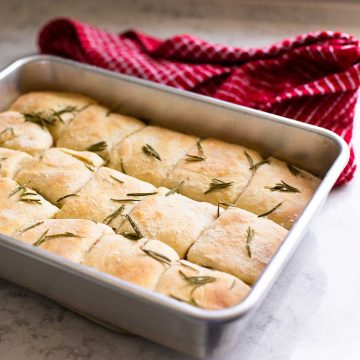 A metal baking pan filled with square-shaped rosemary dinner rolls with roasted herbs over the top.