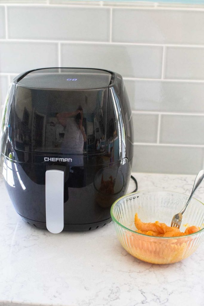 A black airfryer sits on a kitchen counter next to a bowl of seasoned chicken tenderloins.