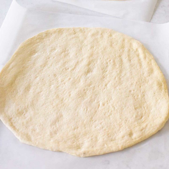 Pizza dough from the bread machine has been rolled out into a circle and is ready for toppings.