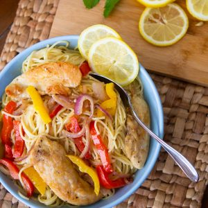 A blue bowl is filled with spaghetti noodles, sliced bell peppers, and chicken tenderloins to show the finished chicken scampi.