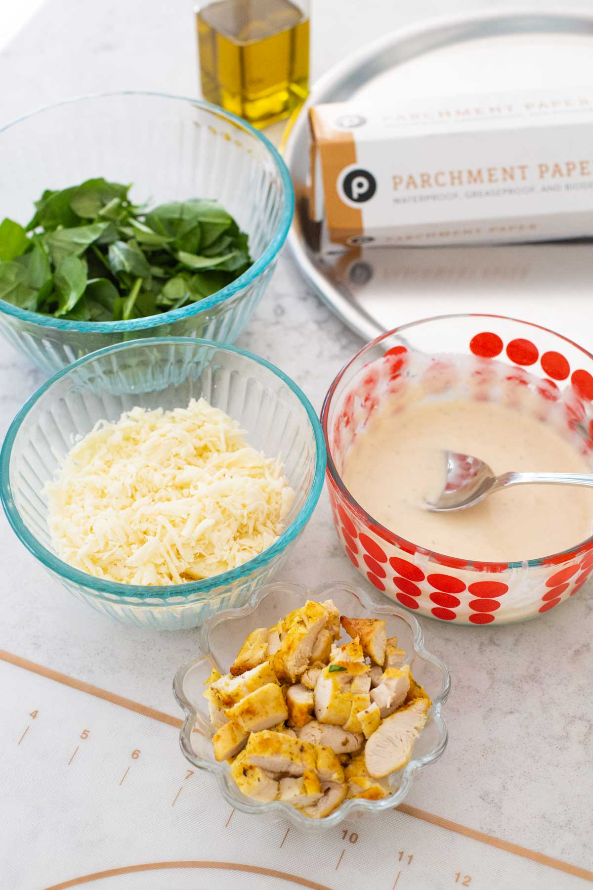 The ingredients for a homemade chicken spinach alfredo pizza are on the counter: a bowl of spinach, shredded cheese, chopped chicken, and homemade alfredo sauce.