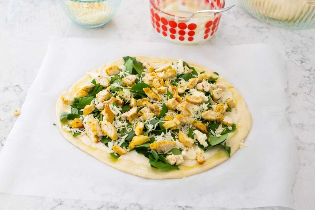 Chicken alfredo pizza has chopped cooked chicken and shredded cheese sprinkled over the top.