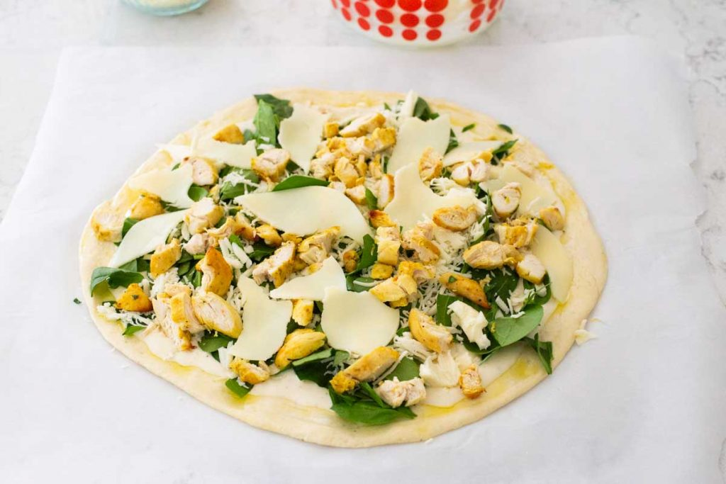 Slices of provolone cheese have been ripped into chunks and tucked into the open spaces on the chicken alfredo pizza.