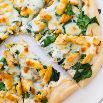 A homemade chicken spinach alfredo pizza has been sliced and the pieces pulled apart.