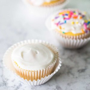 A plain cupcake has a simple white glazed frosting top and sits in a white wrapper. There's a sprinkled cupcake in the back.