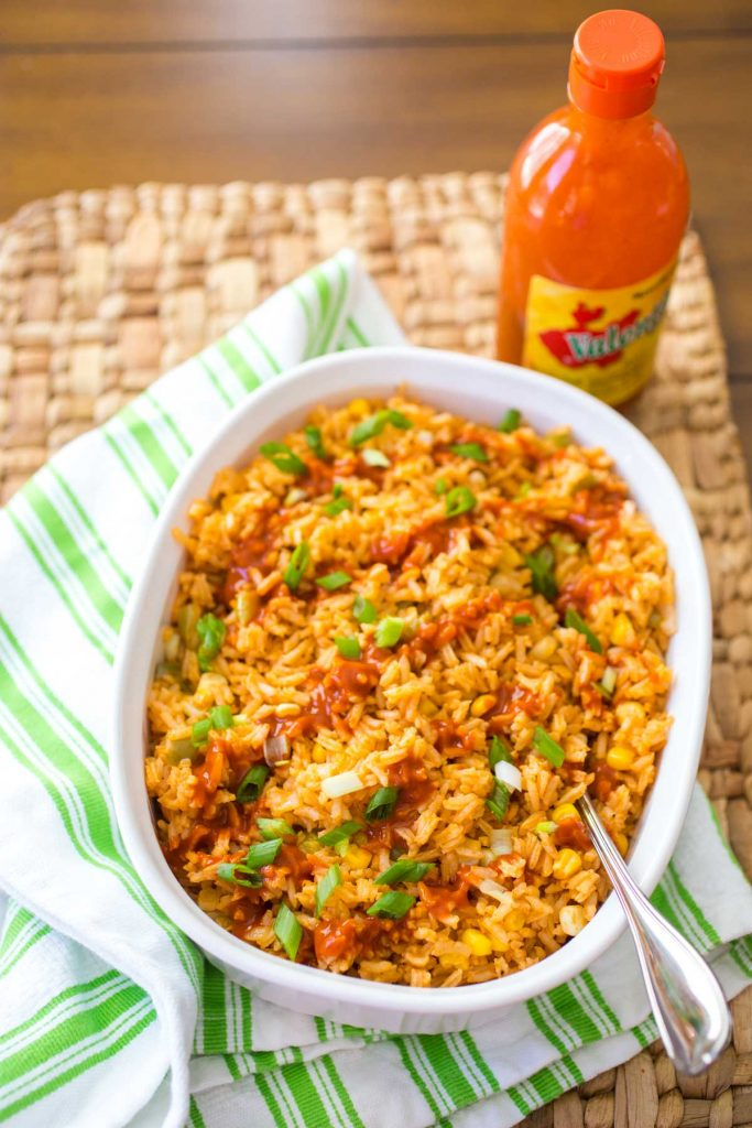 A white baking dish is filled with finished Mexican Rice. Valentina hot sauce is drizzled over the top and chopped green onions are sprinkled for garnish.