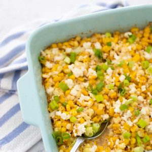 A blue baking dish with yellow Mexican Street Corn casserole has crumbled cheese and fresh green onions sprinkled over the top.