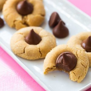 A platter of peanut butter blossom cookies have a Hershey kiss pushed into the top. The front one has a bite out of it.
