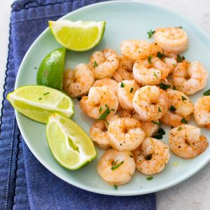 A blue plate with roasted shrimp next to lime wedges. Fresh parsley is sprinkled over the top. A blue napkin is under the plate.