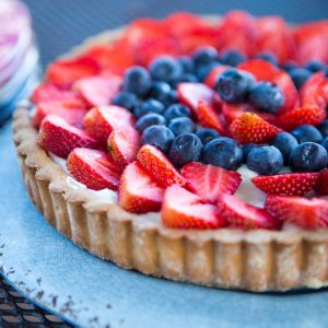 A blue plate with a strawberry tart featuring a cookie crust, creamy filling, and fresh summer berries in a red and blue pattern on the top.