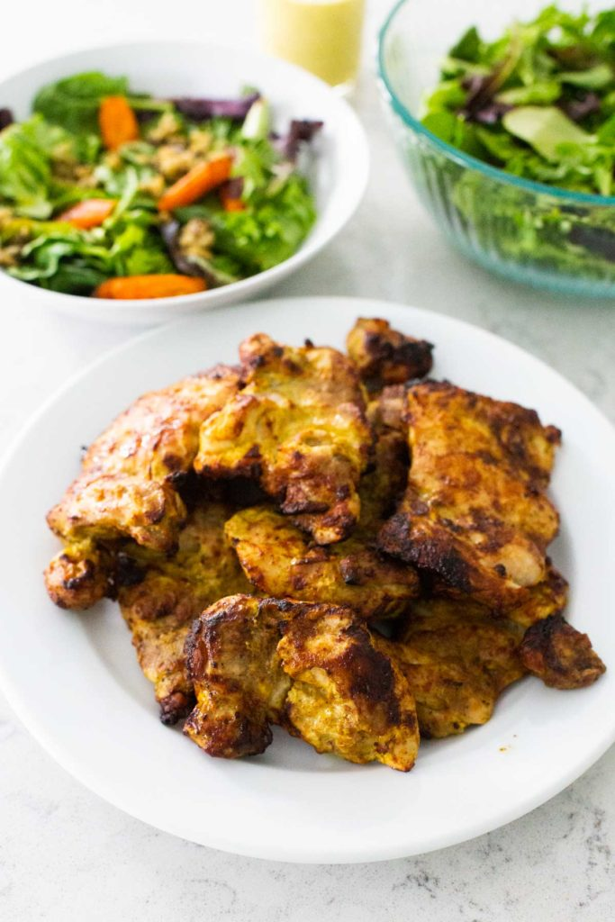 The finished tandoori chicken is ready to be served for dinner with a green salad.