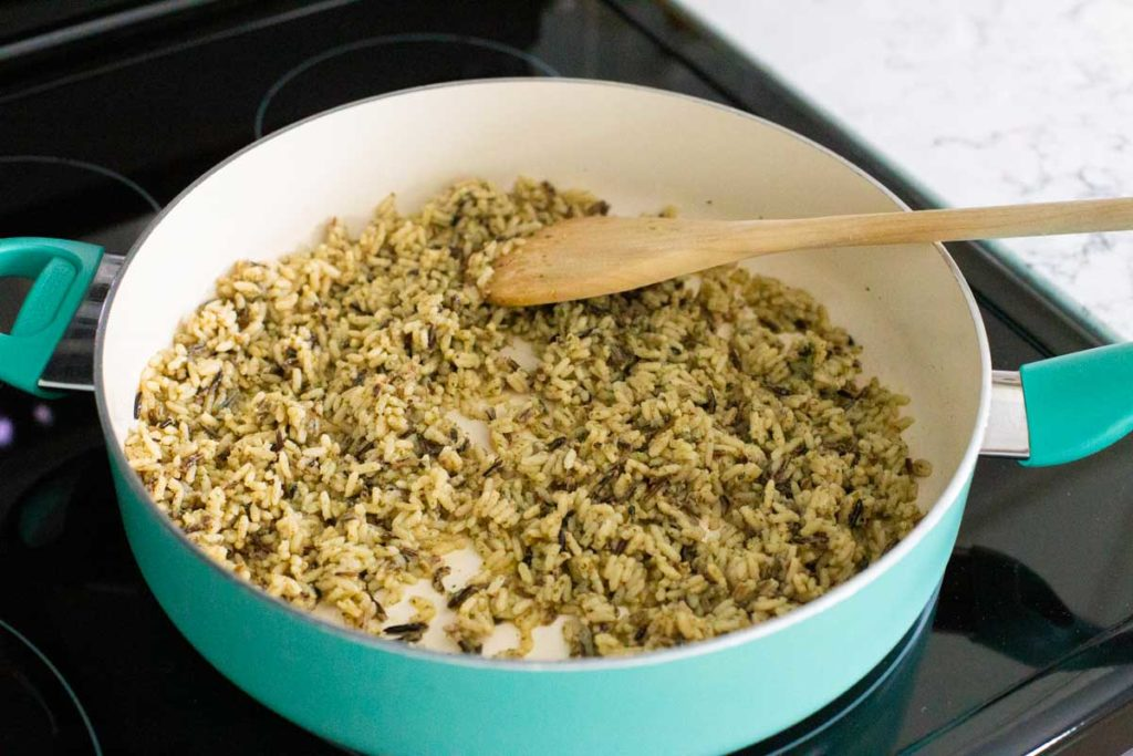 Wild rice is being fried in olive oil in a blue skillet. A wooden spoon is stirring the rice.