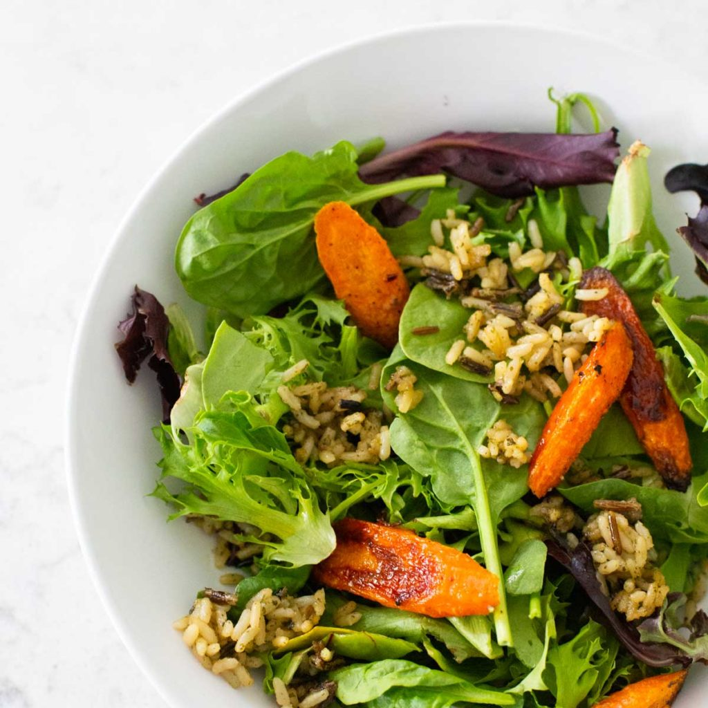A serving of crispy rice salad shows green lettuce, roasted carrots, fried wild rice in a white bowl.