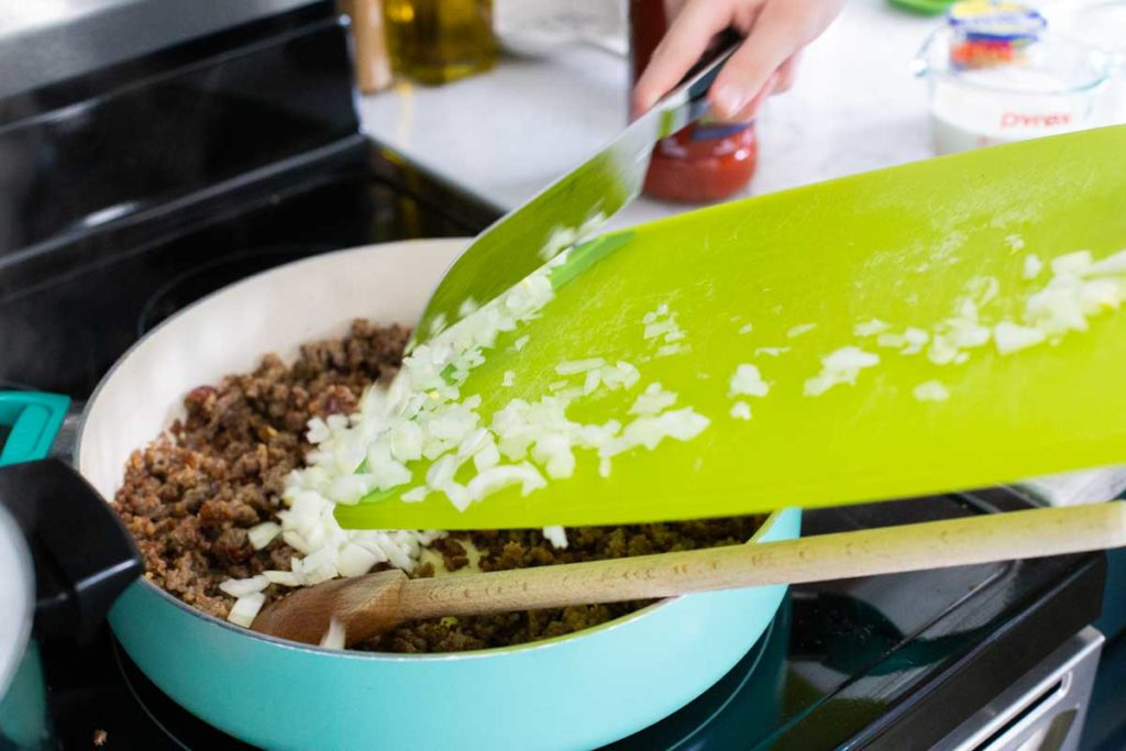 Step 2: Add the chopped onions and garlic. A hand is scraping onions from a cutting board into the skillet.