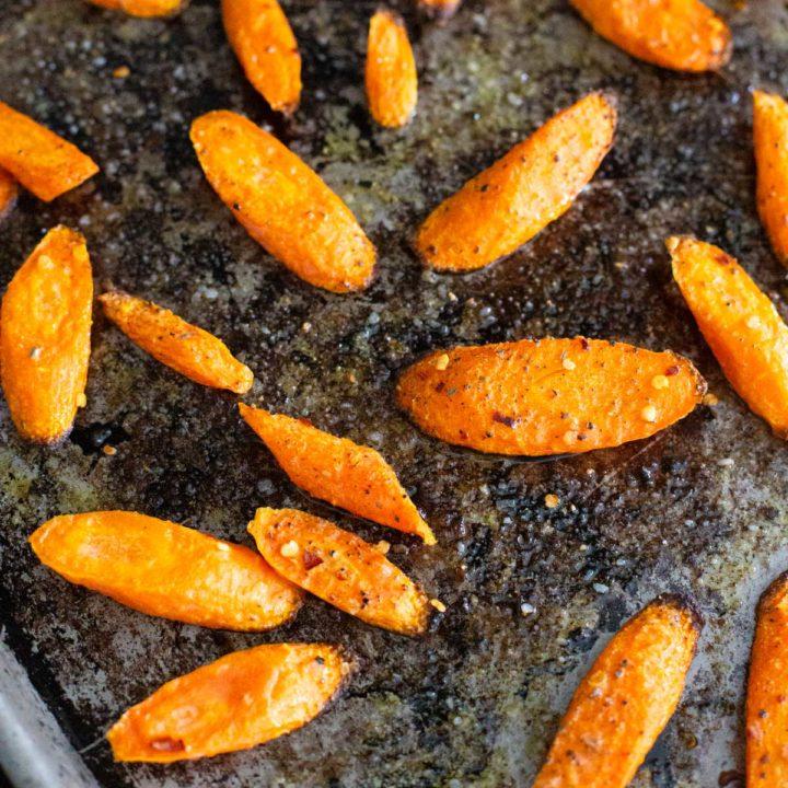 A roasting pan has crisped roasted carrots sprinkled with seasonings.