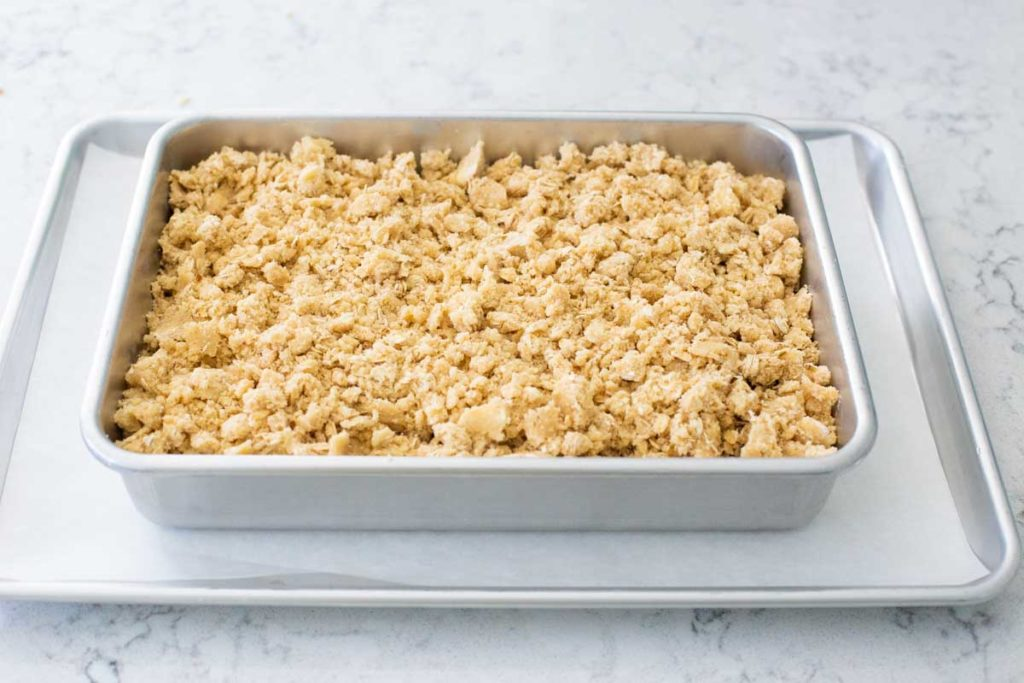 The assembled cherry crisp is ready for the oven and sits on a baking sheet lined with parchment paper.
