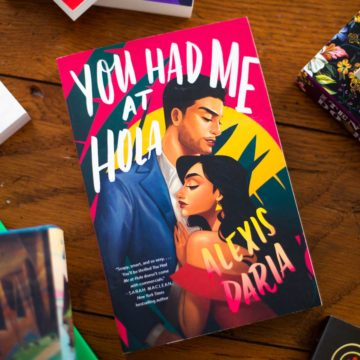 """The book """"You Had Me At Hola"""" sits on a table."""