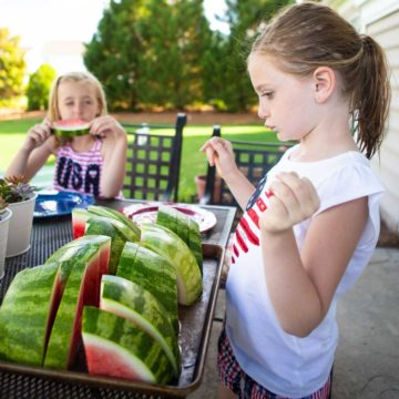 A young girl picks a slice of watermelon from a tray in the backyard.
