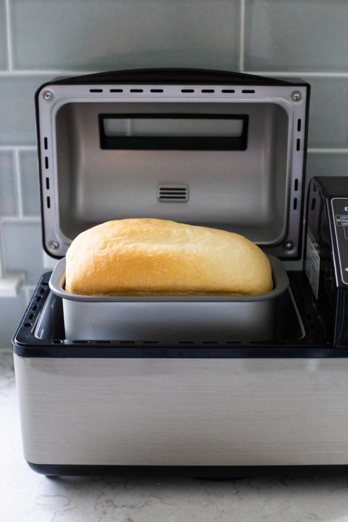 A finished loaf of bread inside the bread machine that baked it.