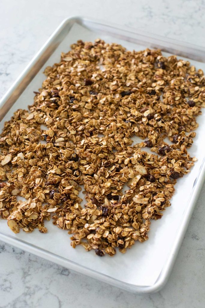 The baking sheet is lined with parchment and has the granola spread in an even layer.
