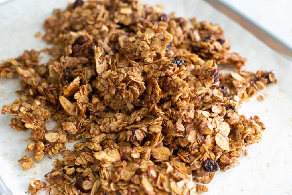 The baked granola is crumbled after cooling.