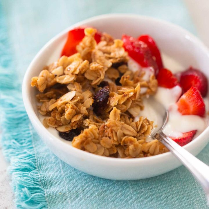 A bowl of yogurt topped with homemade granola and fresh strawberries sits on a blue napkin.