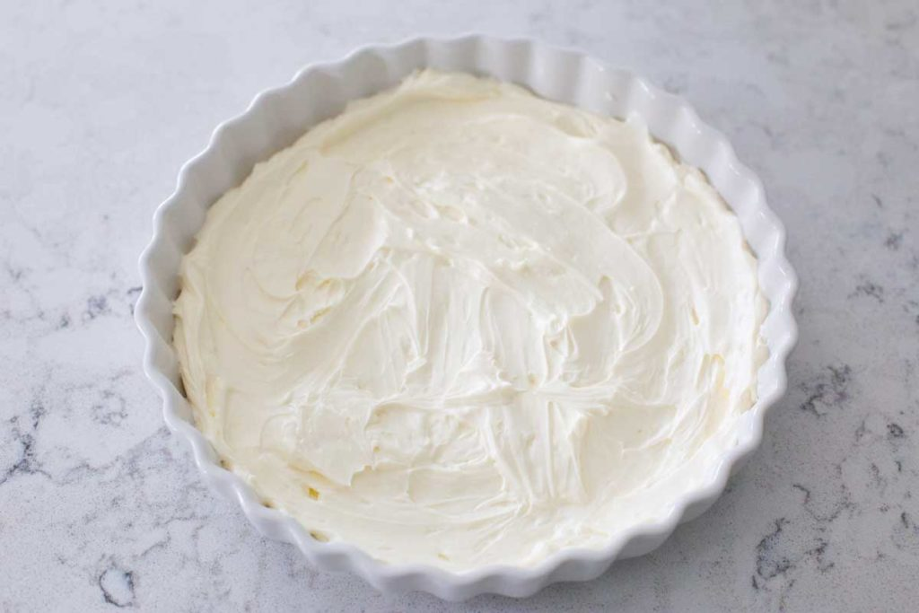 A pie plate has the cream cheese base spread out for the layer dip.