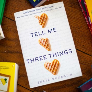 A copy of Tell Me Three Things sits on a table.