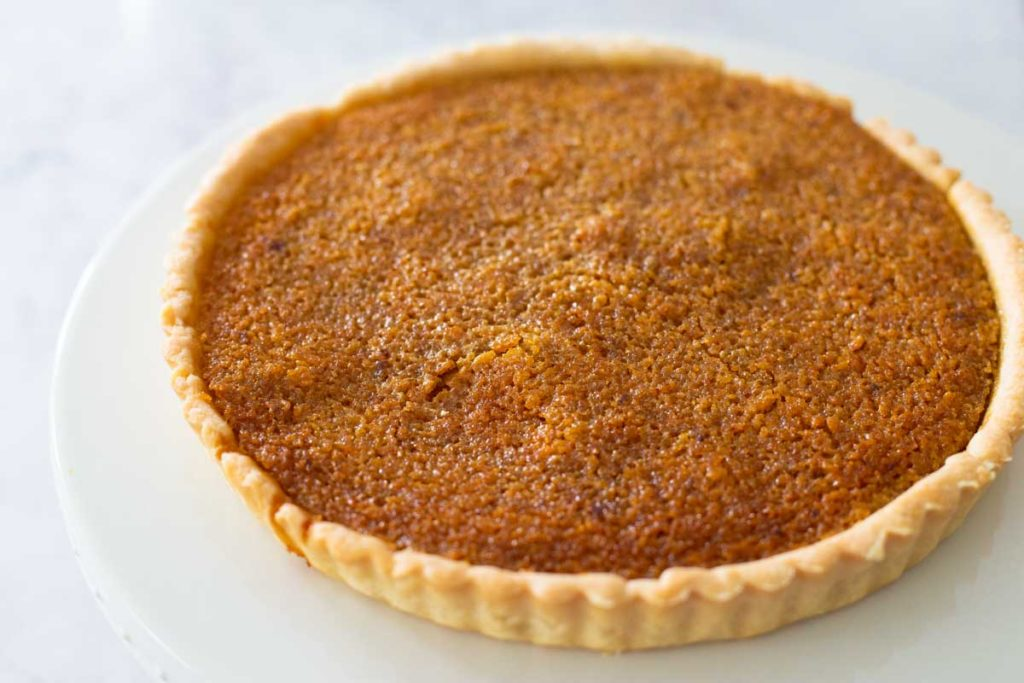The finished treacle tart is on a cake plate.