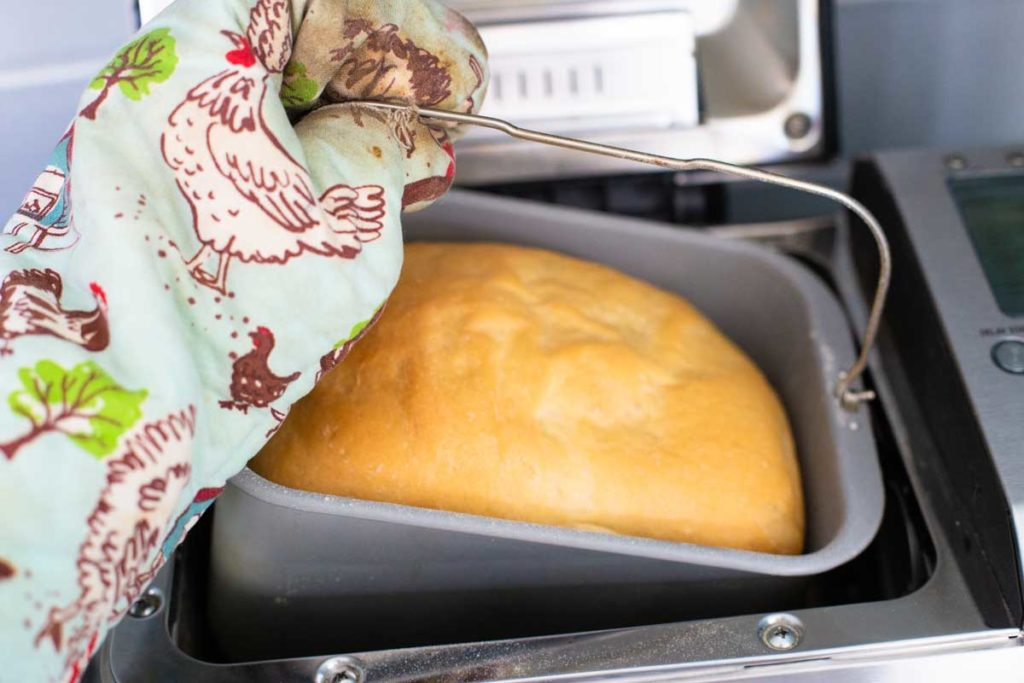 A finished loaf of bread is being pulled out of the bread machine by a hand covered in an oven mitt.