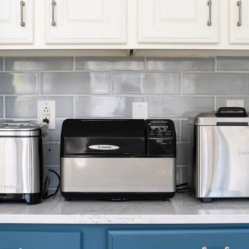 3 bread makers sit on a kitchen counter.