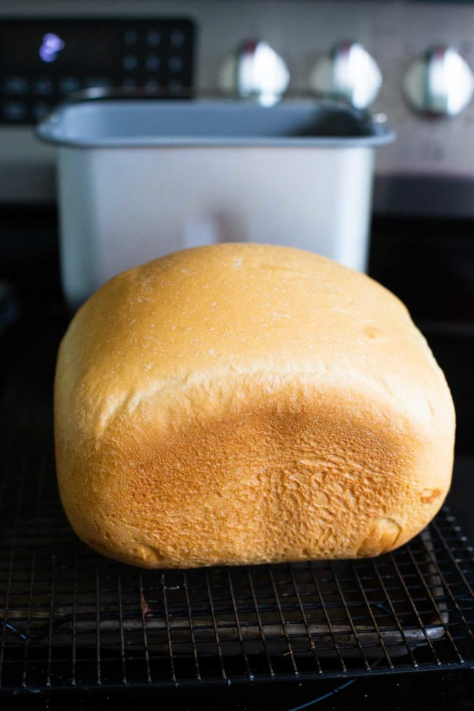 The baked Italian bread sits in front of the bread machine pan.