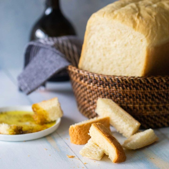 A loaf of bread machine Italian bread sits in a basket next to a few sample wedges near a plate of olive oil for dipping.