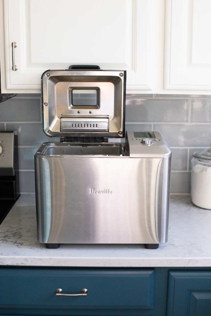 The Breville machine has been pulled forward so the lid can be opened.