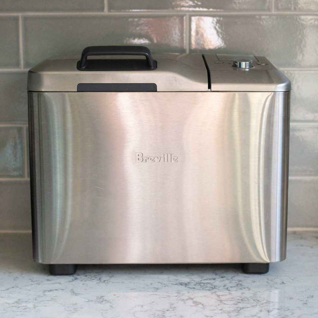 The Breville bread machine sits on a kitchen counter.