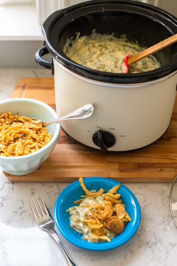 The open crockpot has a serving spoon ready and sits next to a portion of green bean casserole.