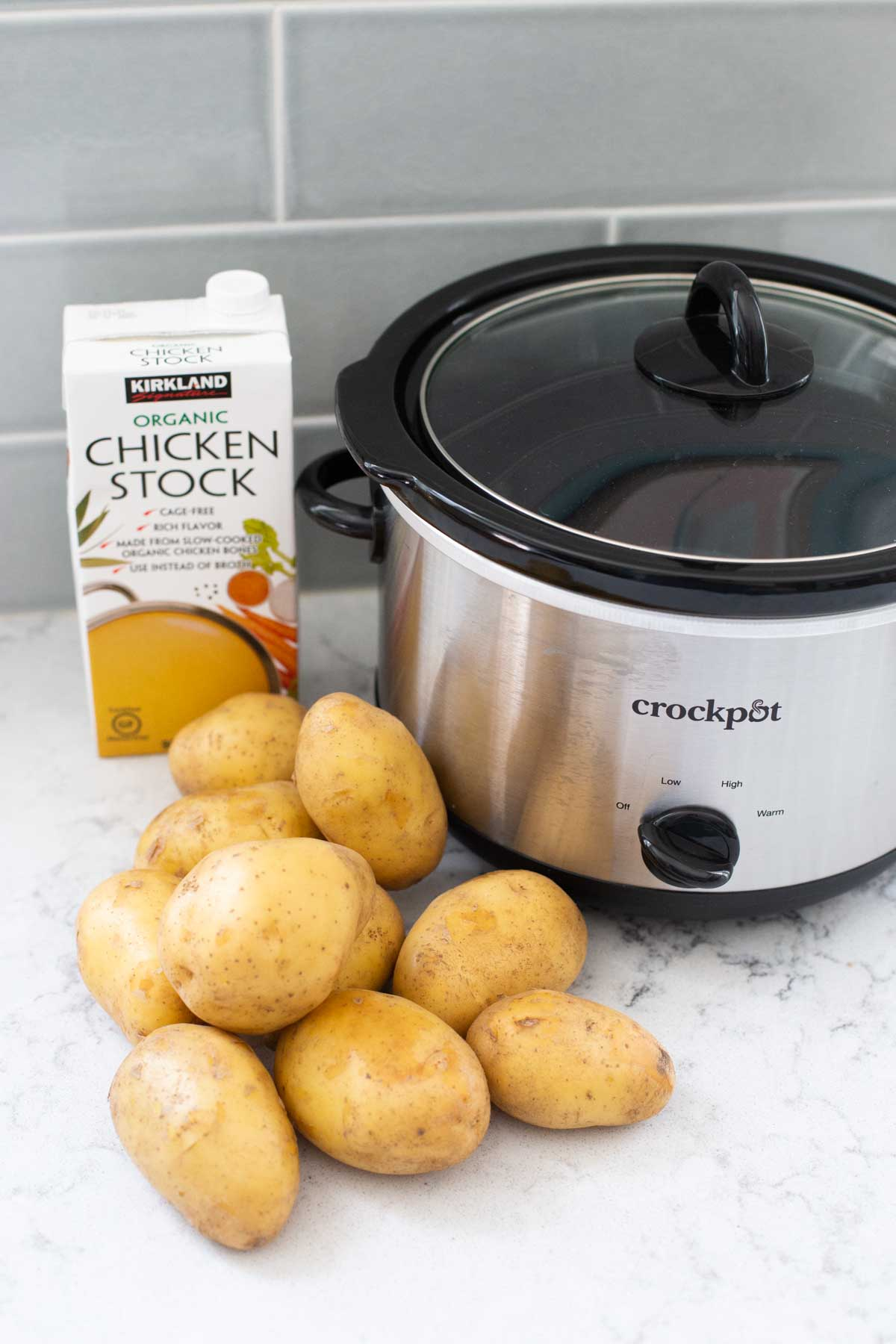 The ingredients for Crockpot mashed potatoes are on a kitchen counter next to a slowcooker.