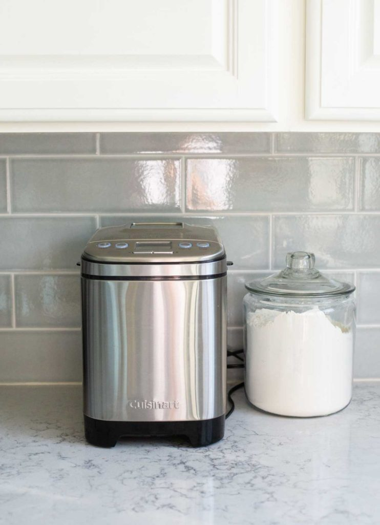 The compact Cuisinart bread machine is on a kitchen counter underneath a kitchen cabinet.