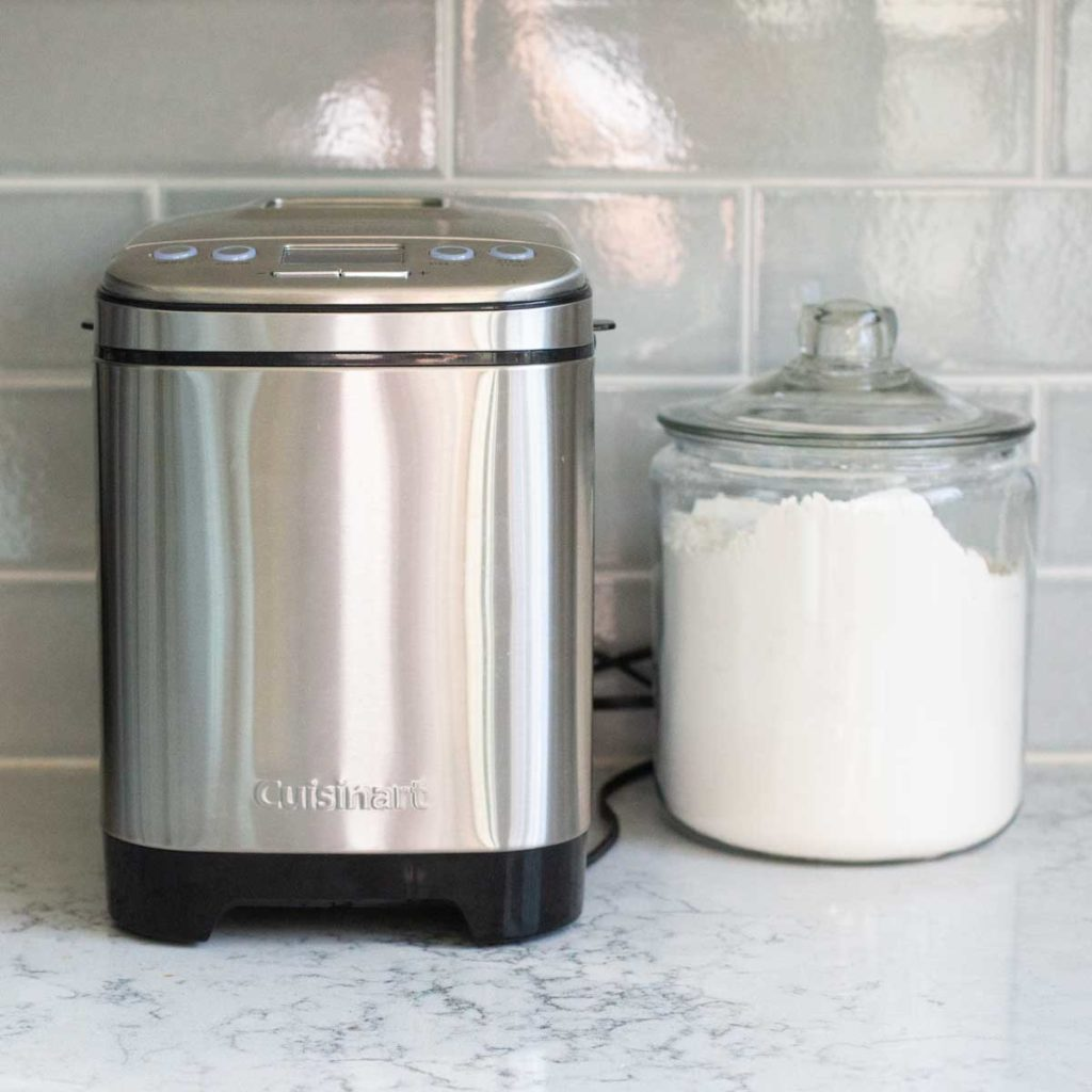 A Cuisinart compact bread maker sits on a kitchen counter next to a jar of flour.