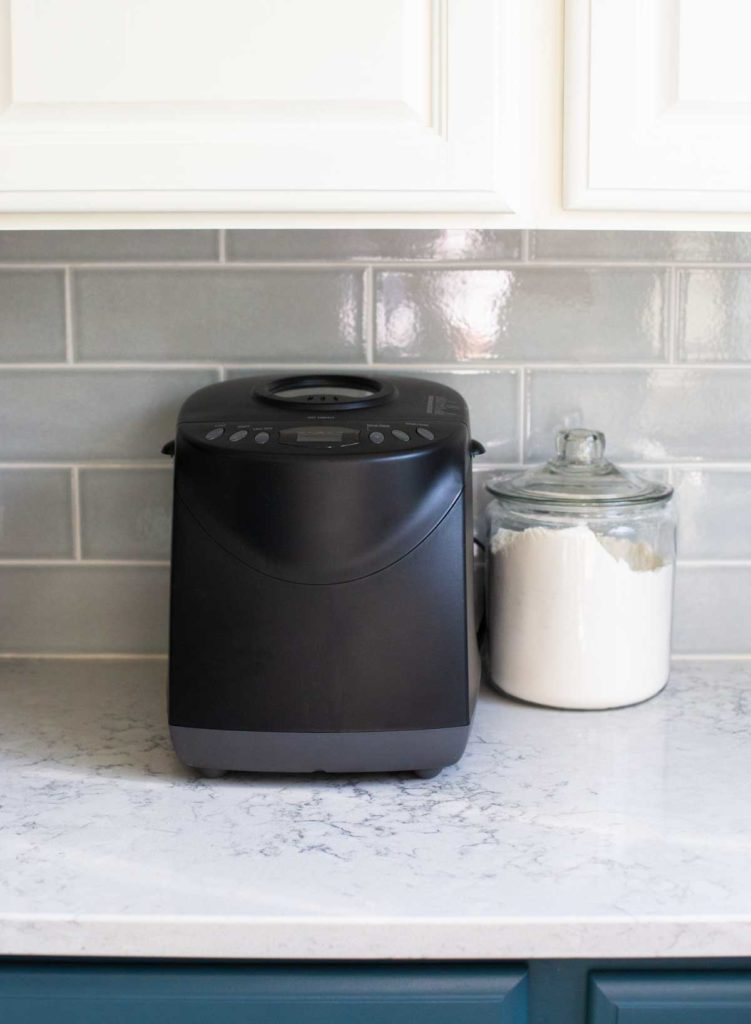 The Hamilton Beach Bread Maker sits on a kitchen counter underneath a cabinet.