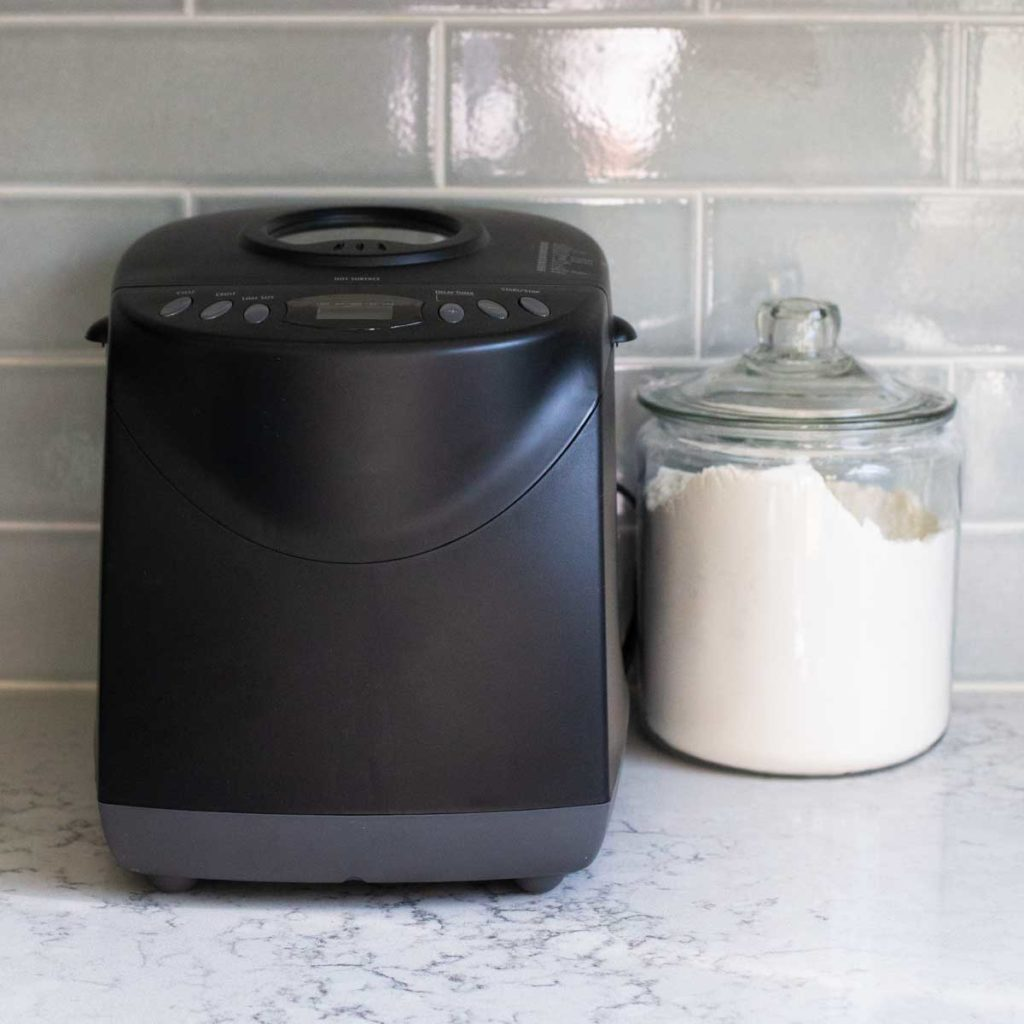 The Hamilton bread machine sits on a kitchen counter next to a jar of flour.